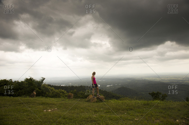 In Las Terrazas, Cuba, a young woman stands at the top of a small mountain overlooking a valley below.
