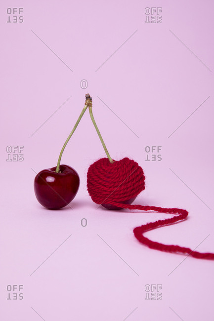 Two red cherries one wrapped in yarn
