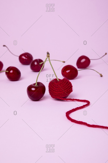 Bunch of red cherries one wrapped in yarn