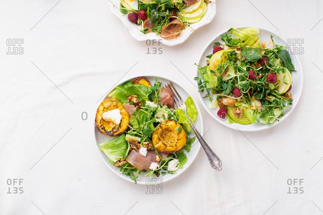 Overhead view of various seasonal summer salads and dressings