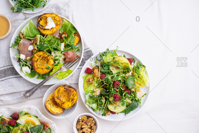 Various summer salads and dressings served on light background