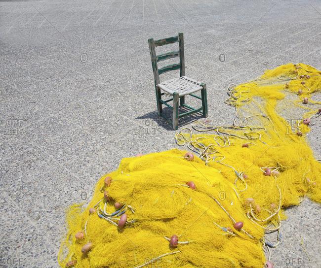 Empty fisherman's chair and a yellow fishing net, Naxos Island, Cyclades, Greece