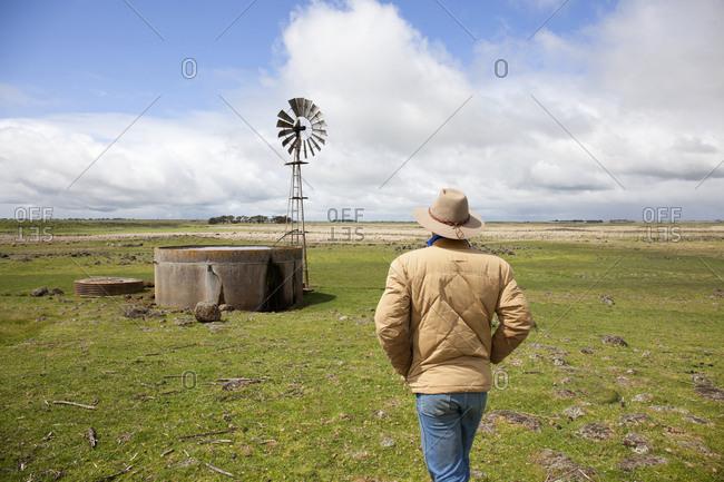 Sheep farmer checking his water supply, Penshurst, Victoria, Australia