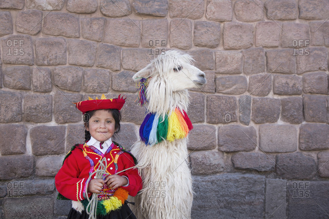 Cusco, Peru - June 26, 2015: Little Peruvian girl in traditional costume with llama