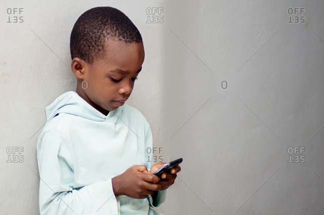 This child is playing a game in the mobile phone.