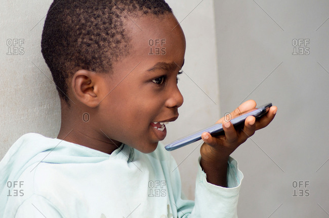 This child speaks directly into the microphone of the mobile phone along with a beautiful smile.