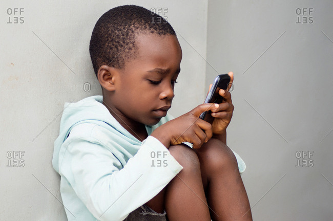 child sitting against the wall manipulating a mobile phone with curiosity.