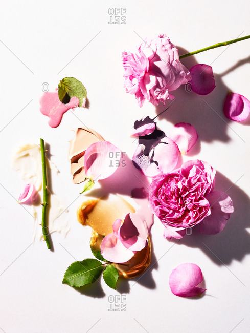 Cosmetic drips and smears on white background with pink rose