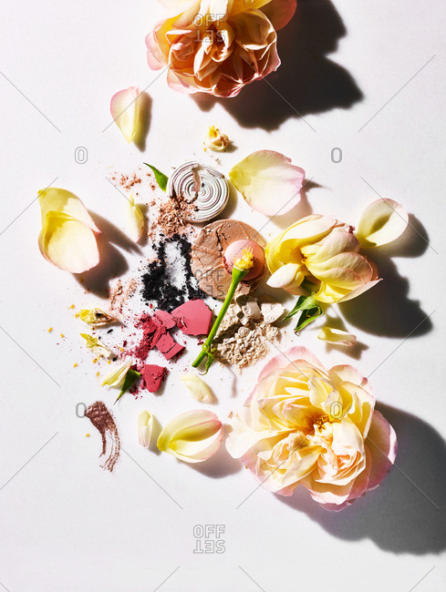 Broken cosmetic powders on white background with pastel roses