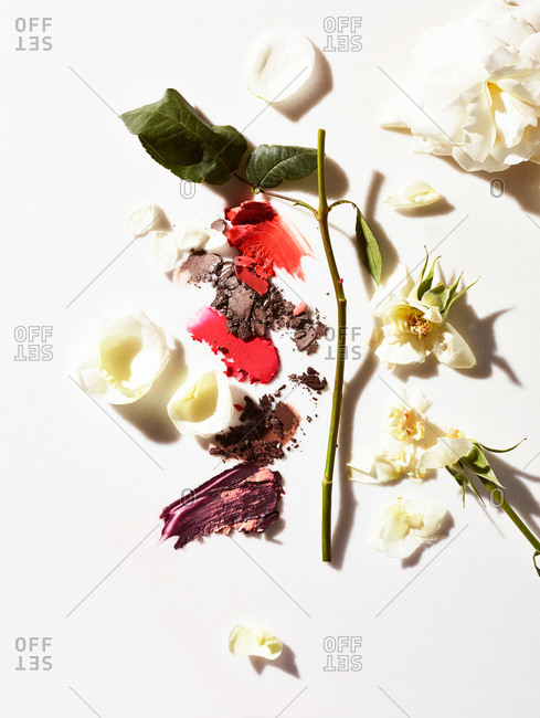 Cosmetic smears on white background with white rose