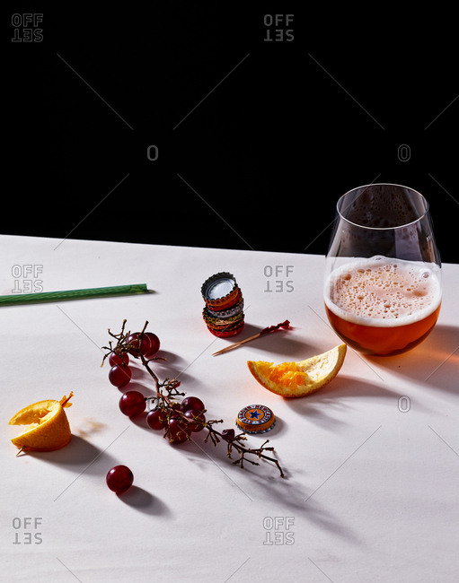 Grapes, orange peels, new castle bottle caps and a glass of beer set on a counter top.