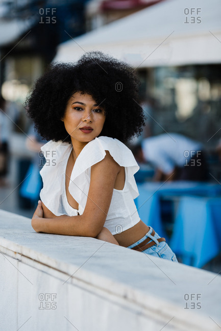 Young African American woman in jeans and crop top relaxing leaning on stone railing and looking at camera outdoors