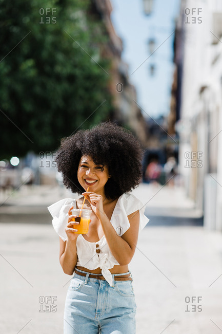 Cheerful trendy African American woman drinking orange juice and looking at camera on urban background
