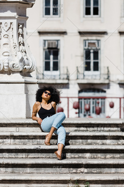 Beautiful ethnic woman in jeans and tank top relaxing and sunbathing on stone stairs against urban background