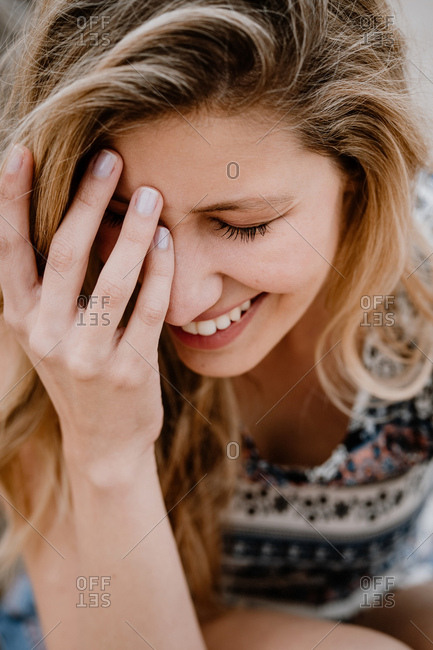 Close-up portrait of young beautiful blonde woman with closed eyes laughing and covering her face with hand