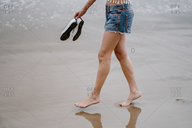 Side view of crop woman in jean shorts walking with shoes in hand on sandy beach