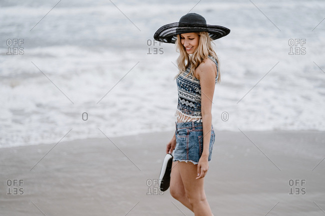 Attractive woman in black hat holding beach bag and shoes while enjoying picturesque view of ocean looking down