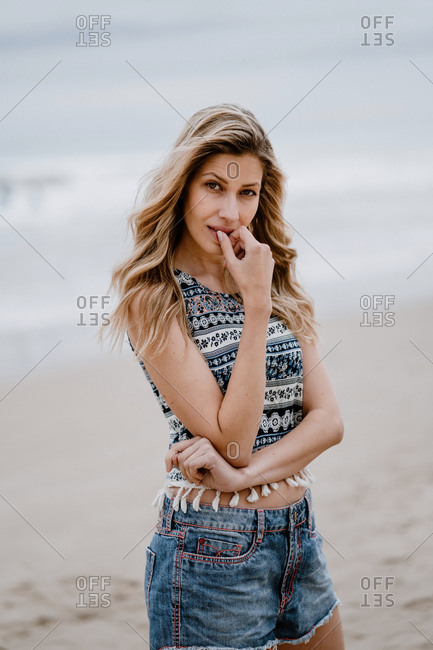 Sensual blonde woman in colorful top and jean shorts posing while relaxing on seashore