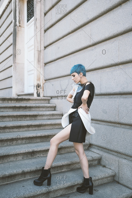 Young woman with short blue hair wearing trendy informal dress and posing provocatively on street steps