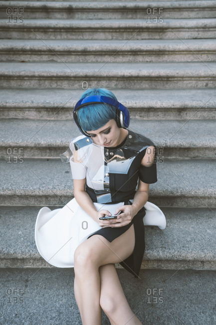 From above of young female with short blue hair and in trendy futuristic dress listening to music with phone on street steps