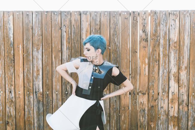 Young female with short blue hair wearing futuristic dress and looking away while standing near shabby lumber fence on city street