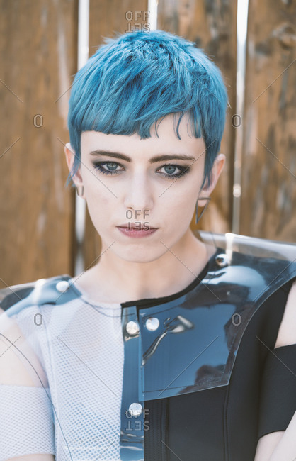 Young female with short blue hair wearing futuristic dress and looking at camera while standing near shabby lumber fence on city street