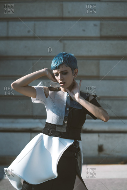 Young lady in futuristic dress touching face and short blue hair while standing near building on sunny day on city street