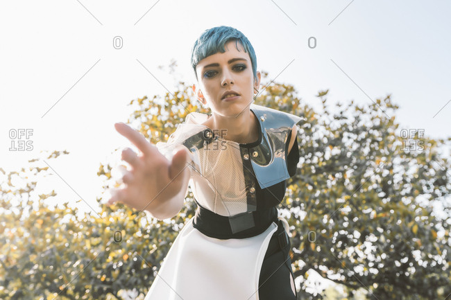 From below young lady with short blue hair and in futuristic dress bending forward and trying to touch camera on blurred background of tree on sunny day in park