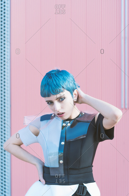 Young woman in trendy alternative dress touching short blue hair and looking at camera while standing against pink wall on city street