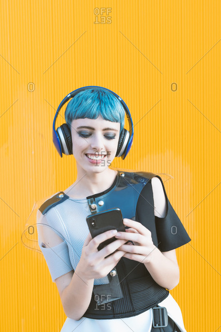 Cheerful informal lady in headphones browsing smartphone and listening to music while standing against vivid yellow wall