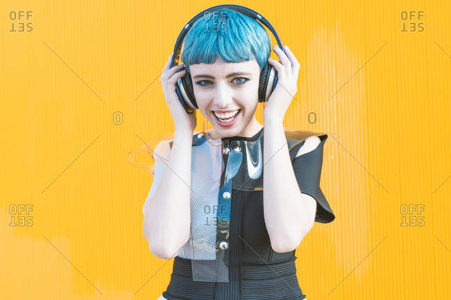 Cheerful young woman in trendy alternative dress smiling and listening to music in headphones against yellow wall