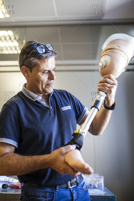 Prosthetic engineer reviewing the prosthesis of a patient and improving the material in his workshop