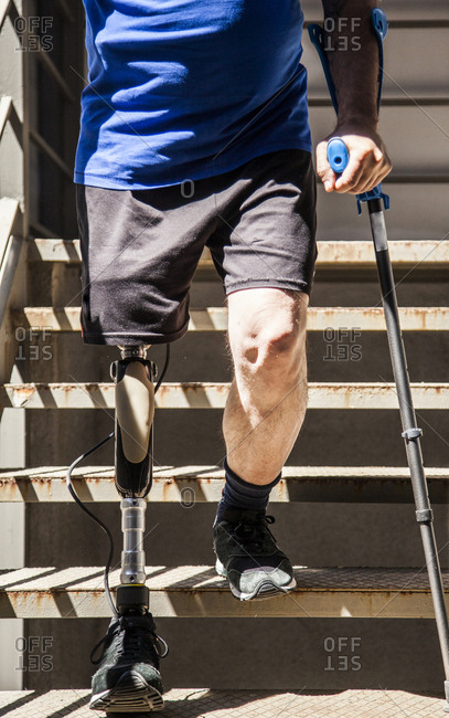 unrecognizable man amputated with crutches testing his new leg prosthesis going down stairs