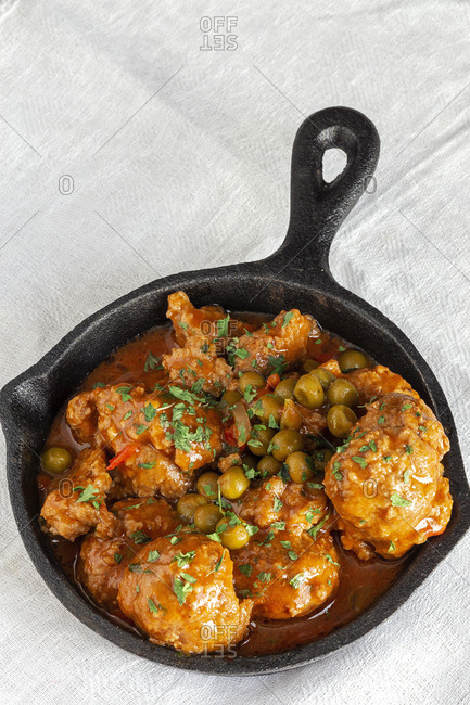 From above hot skillet with cooked delicious meatballs and green peas on white tablecloth