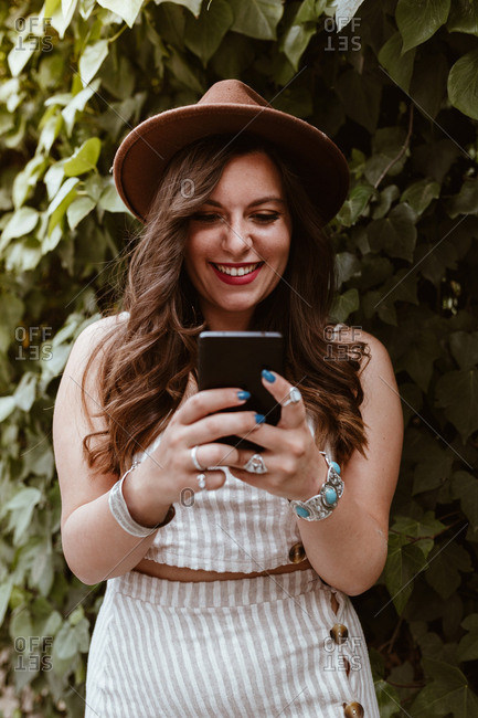 Long haired attractive woman in hat messaging in mobile phone with wide smile