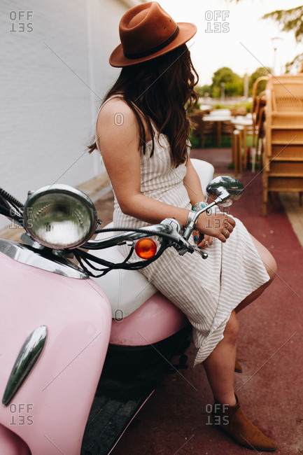 Side view of unrecognizable fashionable woman sitting on pink motorbike in street