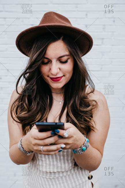 Long haired attractive woman in hat messaging in mobile phone