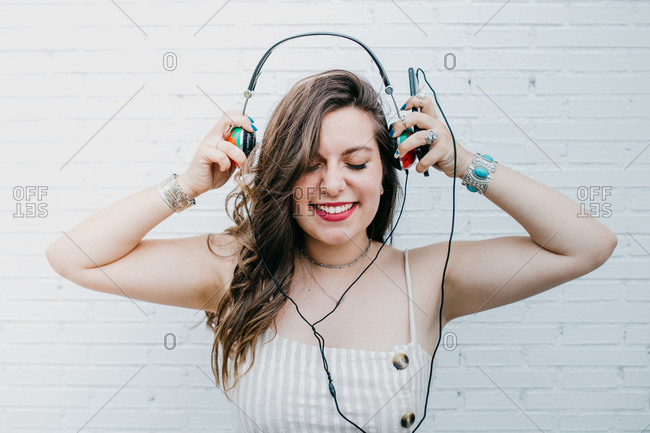 Smiling attractive youngster woman with closed eyes putting headphones on to listen to music on smartphone on white background
