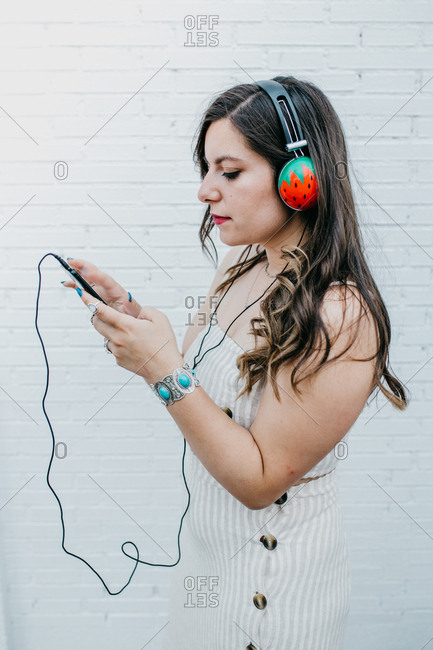 Side view of long haired attractive youngster woman checking play list in smartphone on white background