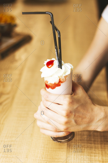 White ice cream in paper cone in hands
