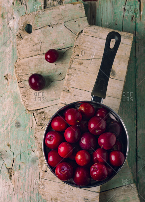 From above saucepan full of sweet fresh plums placed on shabby wooden boards