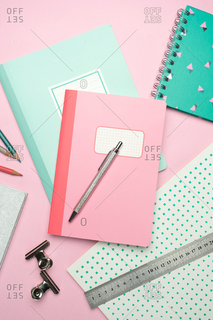 From above composition of colorful notebooks, pen, pencils, ruler and paper clips arranged on pink desk