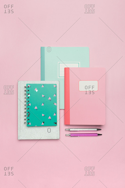 From above composition of colorful notebooks and paper clips arranged on pink desk