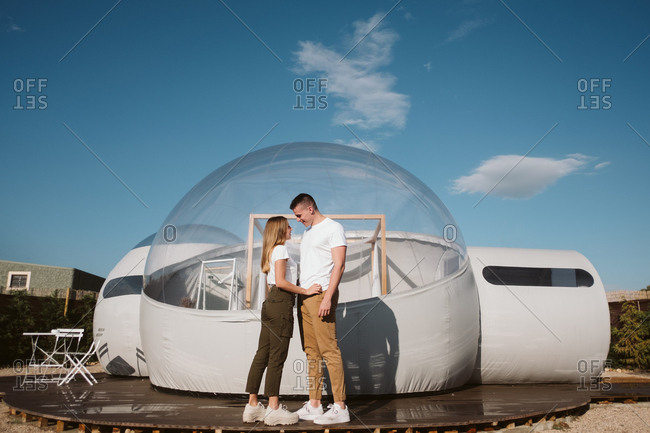 Side view of passionate man and young woman while standing in front of romantic transparent glamping