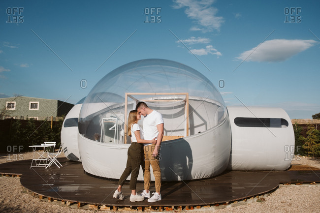 Side view of passionate man holding and kissing young woman while standing in front of romantic transparent glamping