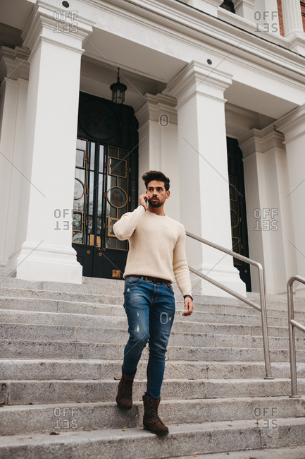Stylish bearded man standing on stairs, talking by mobile phone outdoors