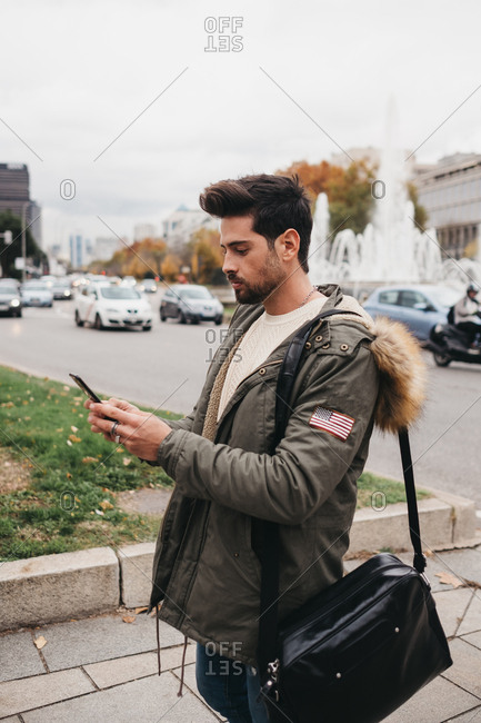 Side view of trendy man in parka standing with mobile phone and searching on urban background