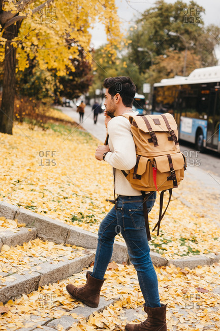 Handsome young man with trendy hairstyle walking on autumn leaves and speaking by smartphone on daytime