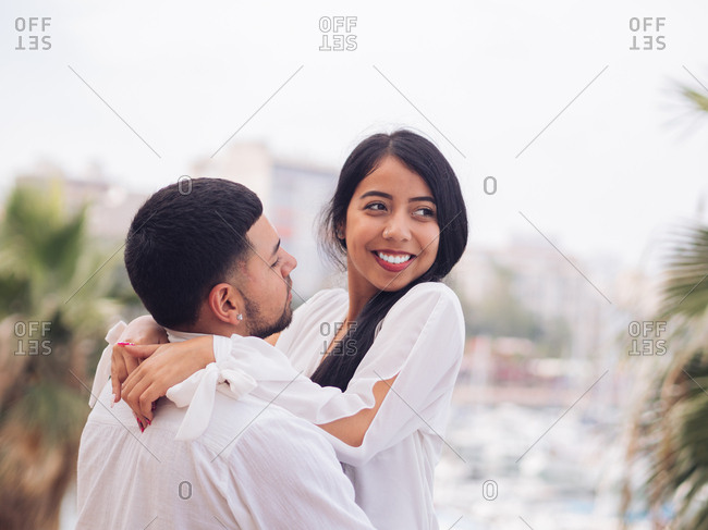Side view of lovely young couple in light clothes bonding and hugging with love and tenderness on dock in port