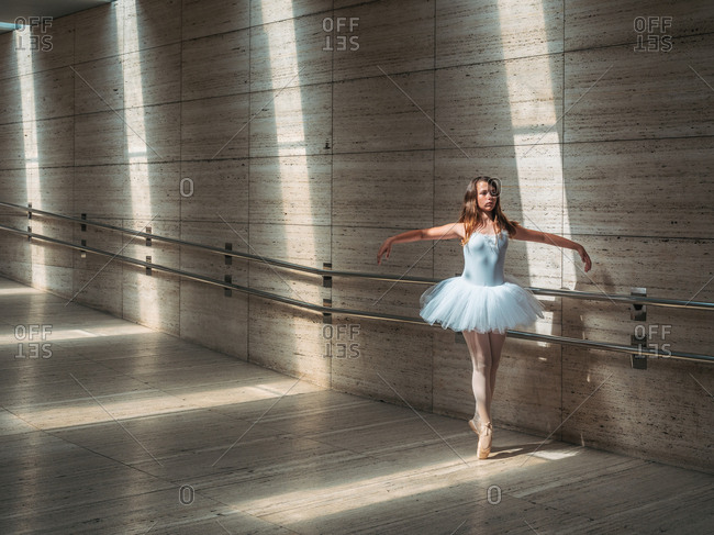 Ballerina in white ballet tutu performing exercises at rail in contrast sunny light